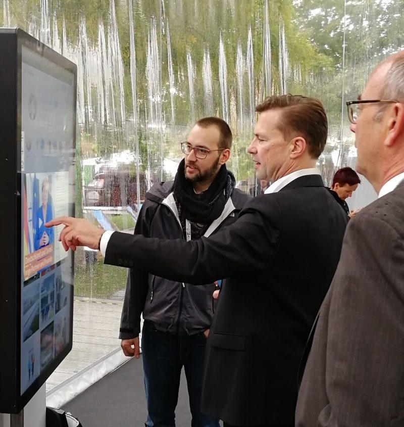 Regierungssprecher Steffen Seibert benutzt Multitouch-Stele zur Präsentation von Social-Media-Aktivitäten der Bundesministerien