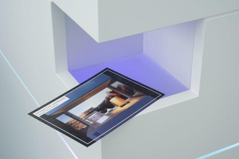 Eine Postkarte wird in die Scanner-Nische des Multitouch-Tisches gehalten