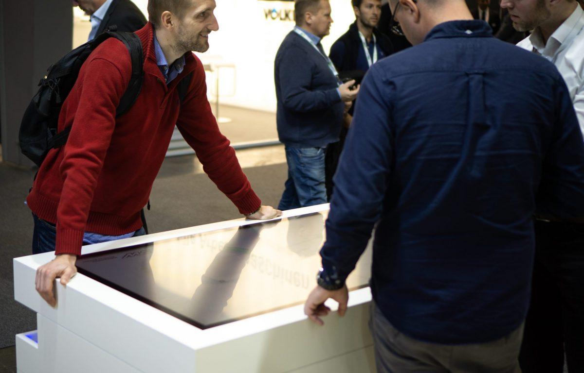 Messebesucher an interaktiven Vertriebs-Stationen