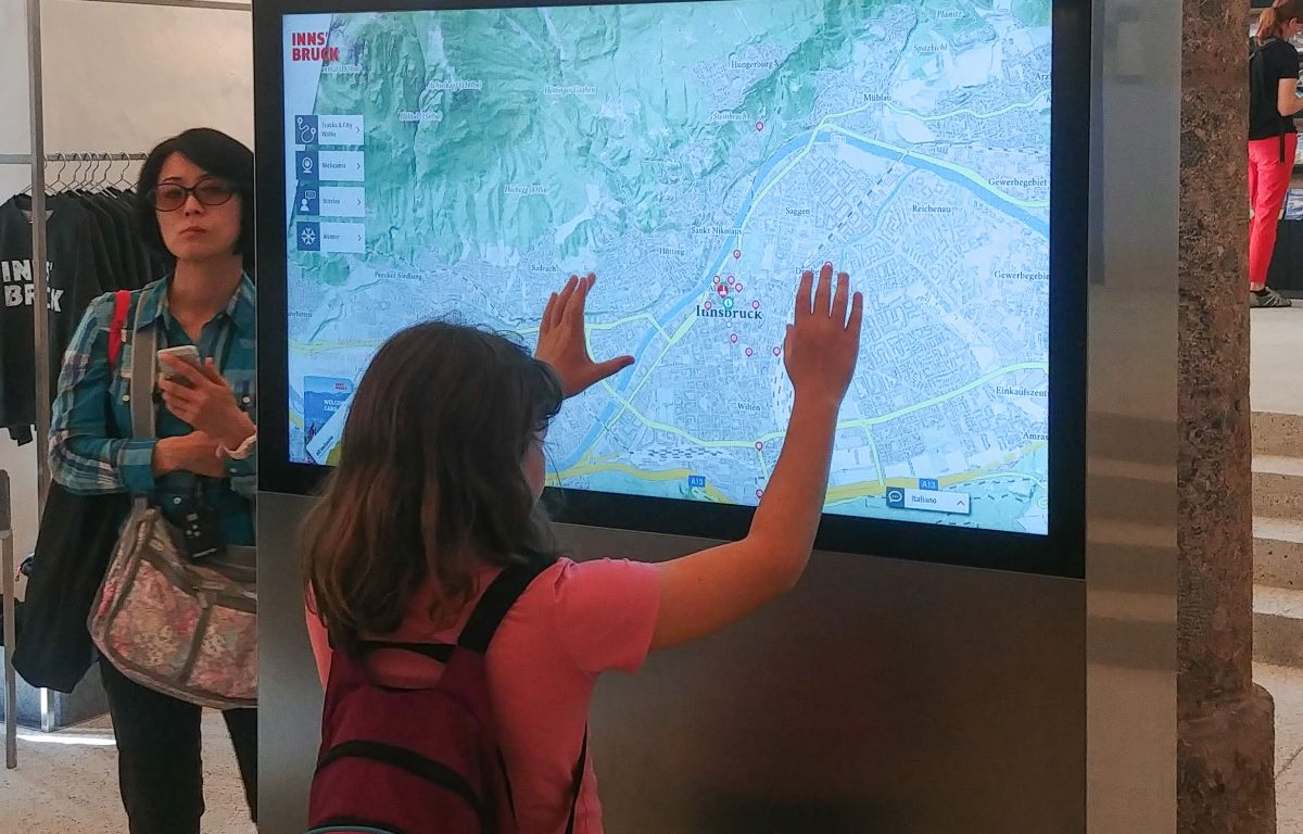 Visitor interacts with map on multitouch monitor at Innsbruck Info