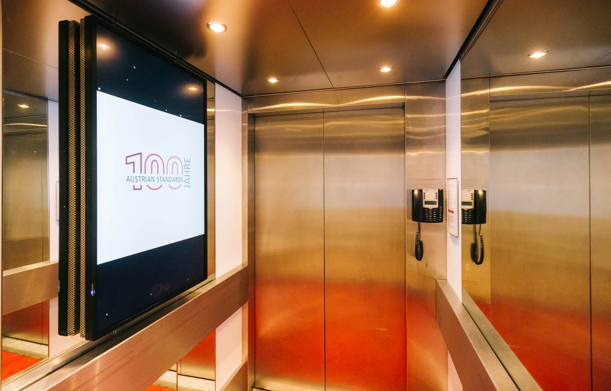 Lifts with glazed screens presenting standards and animated information