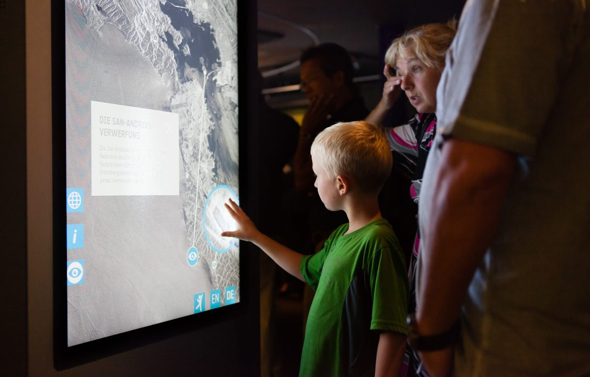 Child touching the multitouch screen of a multitouch stele in the exhibition