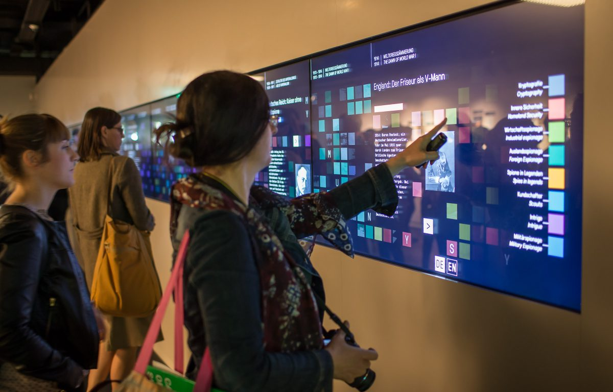 Museum visitor touches multi-touch wall in the German Spy Museum