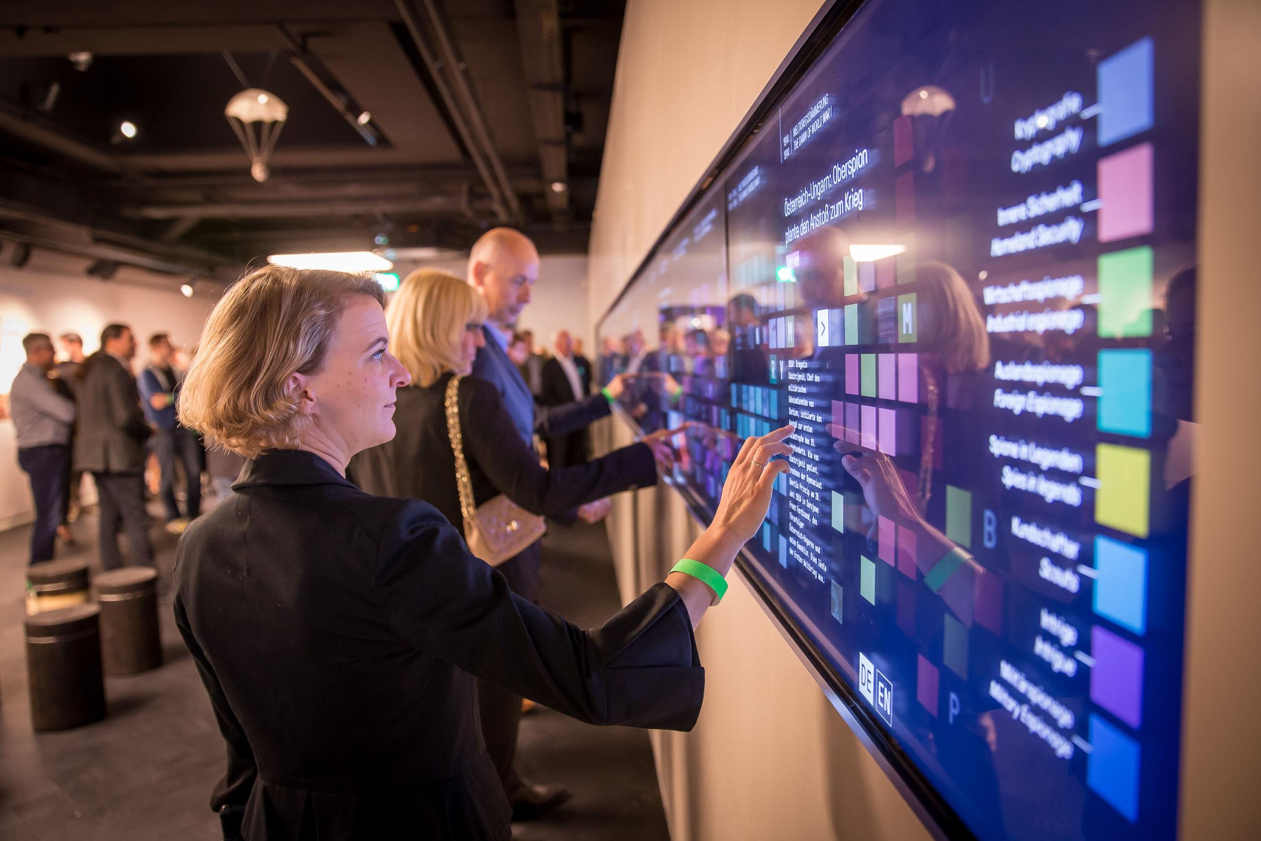 Besucher interagieren mit großer Multitouch Wall im Deutschen Spionagemuseum