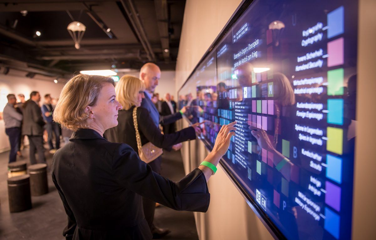 Visitors interact with large multi-touch wall in the German Spy Museum
