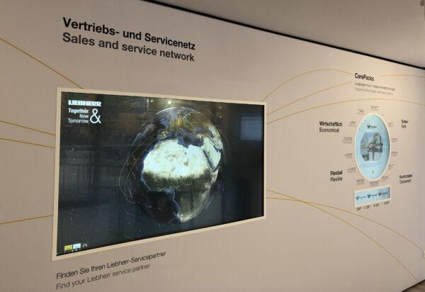 interaktive Messewand mit eingelassenen Multitouch-Screens und rundem Monitor