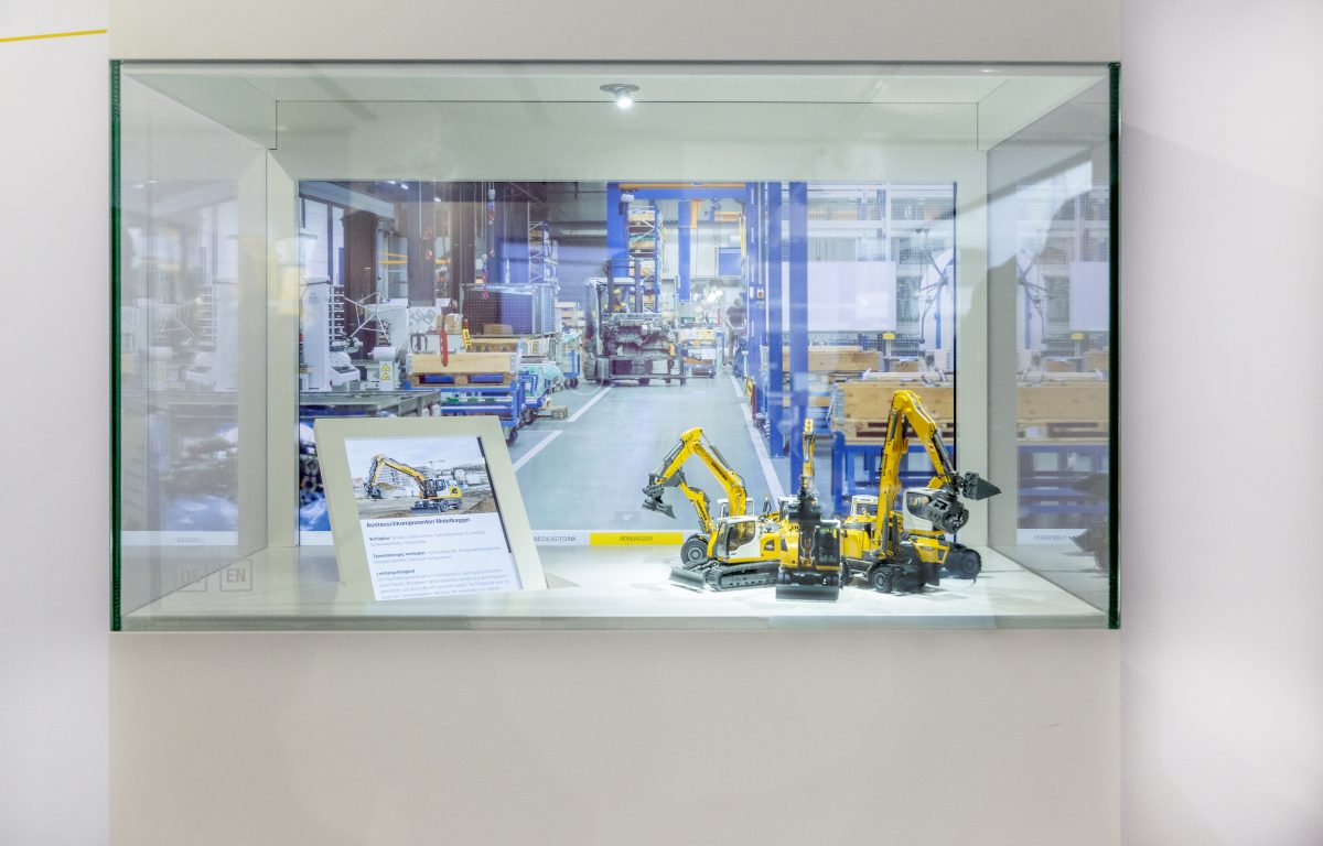 Select excavator by swiping gesture on the showcase glass and receive information on two monitors
