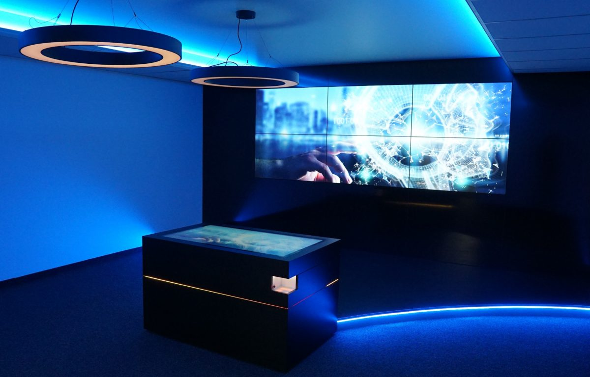 Multitouch-Tisch mit Bildschirmwand in interaktivem Showroom