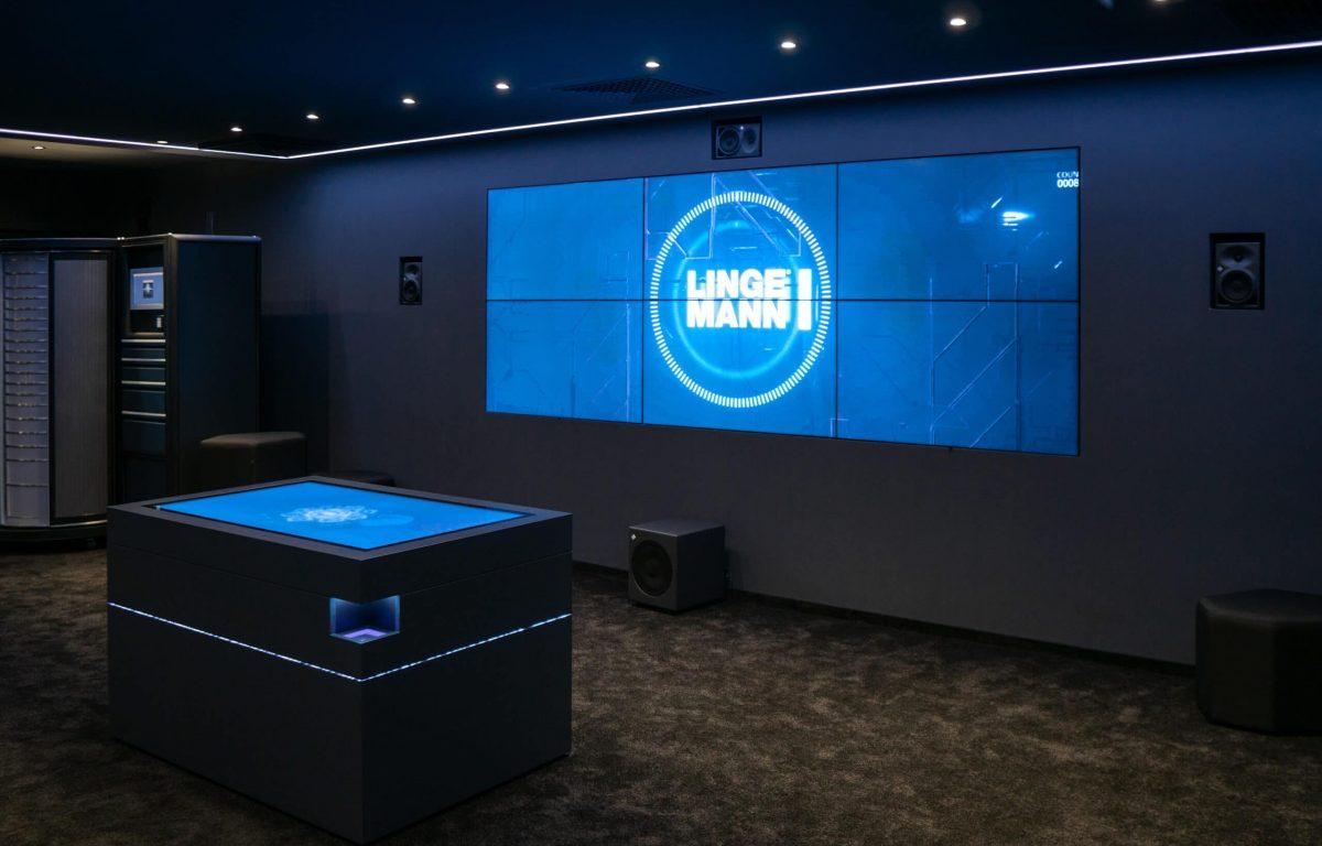Lingemann Showroom mit Bildschirmwand und interaktivem Tisch zur Produktpräsentation