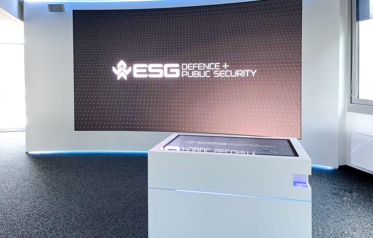Showroom mit LED-Wall und interaktivem Touch-Tisch in weißem Design